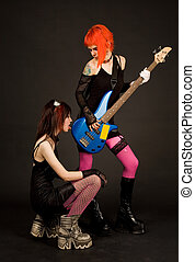 Two rock girls, one of them licking guitar