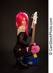 Attractive girl with bass guitar isolated on black...