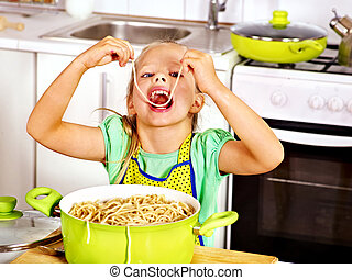Children cooking at kitchen - Children eating spaghetti at...
