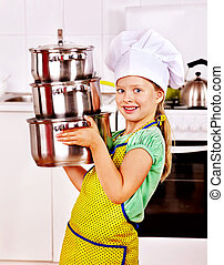 Child cooking at kitchen - Child wearing hat and apron...