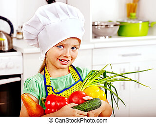 Child cooking at kitchen. - Child holding vegetable at...
