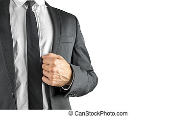 Successful businessman holding the lapel of his suit jacket...