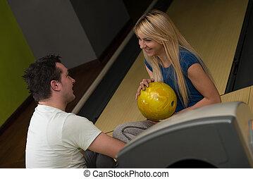 Man Teaching Woman Bowling - Beautiful Young Woman Is...