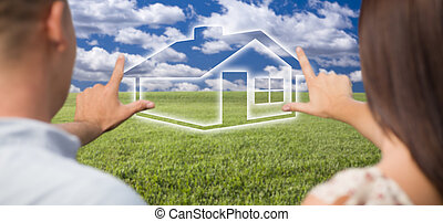 Couple Framing Hands Around House Figure in Grass Field -...