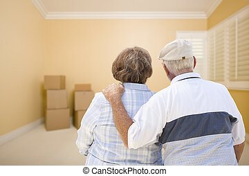 Senior Couple In Room Looking at Moving Boxes on Floor -...