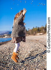 Adorable little girl on the beach having fun at warm winter day