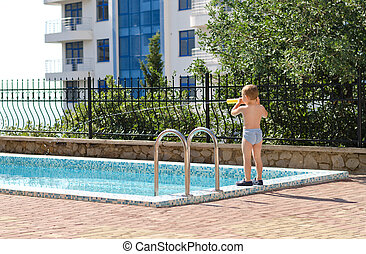 Young boy standing at the edge of a pool