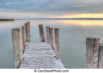 Wooden pier on the lake at sunset