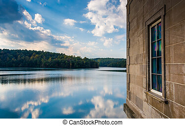 Side of a building and reflections in Prettyboy Reservoir,...