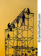 Silhouette of Workmen on assembling concert stage -...