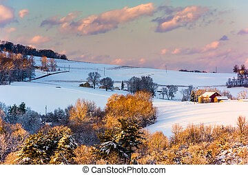 Snow covered hills and farm fields at sunset, in rural York...