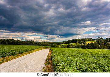 Stormy sky over a country road and farm fields near Cross Roads, Pennsylvania.