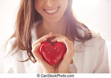 Holding heart - Close-up of smiling female holding red heart