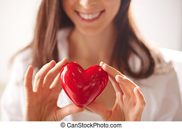 Red heart - Close-up of smiling female holding red heart