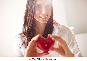 Happy woman - Image of smiling female with red heart in...