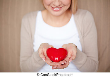 Holding red heart - Close-up of smiling female holding red...
