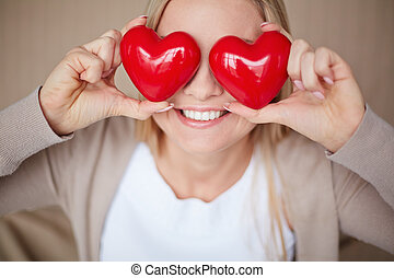 In love - Image of smiling female with two red hearts by her...