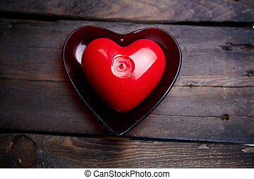 Romantic candle - Image of red heart shaped candle on wooden...