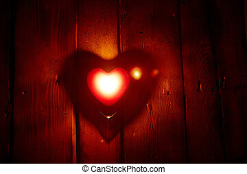 Candle burning - Image of red heart shaped candle burning on...