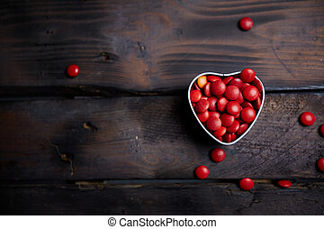 Love drage - Red small candies in heart shaped box against...