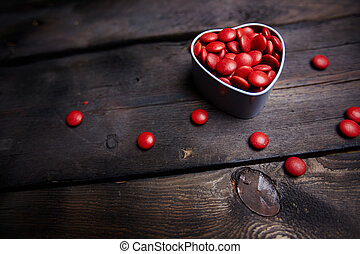 Sweet love - Red small candies in heart shaped box against...