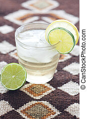 water with lemon and lime in a glass with ice on ethnic mat