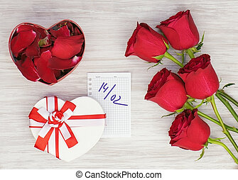 Valentine`s Day gift, roses and paper on wooden background.