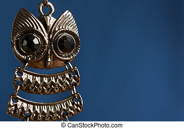 Earring in the form of an owl on a blue background