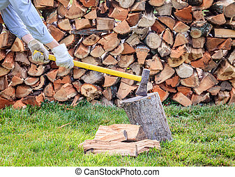 Splitting firewood - A man is splitting firewood outdoors