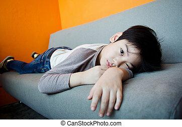 Boring asian boy - Asian boy sleeping on a Sofa bench with...