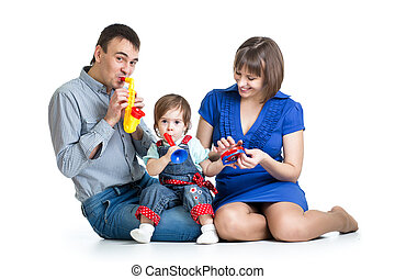 Mother, father and kid girl having fun with musical toys. Isolated on white background