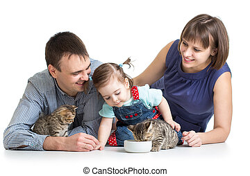 kid girl and her parents feeding small kittens