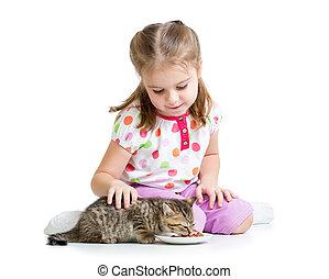 little girl feeding cat kitten