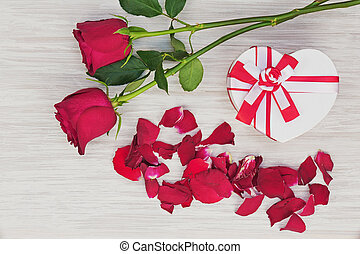 Valentine`s Day gift and roses on wooden background.