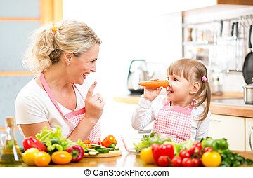 mother and child preparing healthy food and having fun