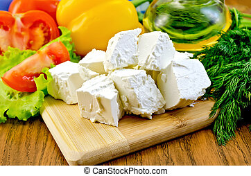 Feta cheese on the board with vegetables and salad - Slices...