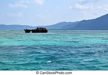 Cobalt blue view - A coral island in a cobalt blue water at...