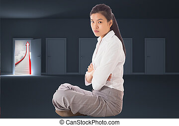 Businesswoman sitting cross legged with arms crossed against...