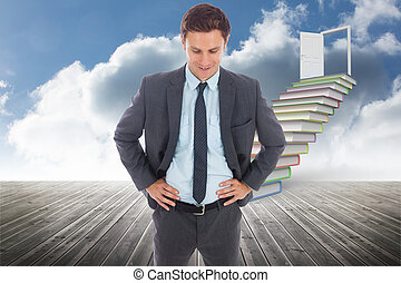 Cheerful businessman standing with hands on hips against...