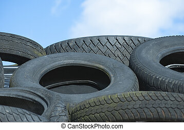 Car Tyres in Recycle Pile against Blue Sky - A recycle pile...