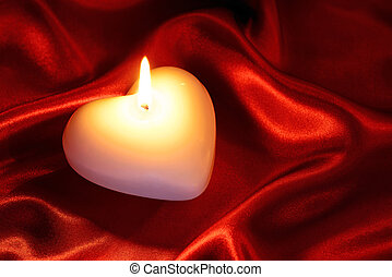 Heart shaped candle on red silk - A white heart shaped...