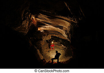 Spelunkers exploring an underground cave hall