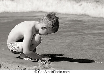 Lonely - Sad, lonely boy on the beach playing with the sand.