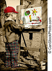 Boy painting his colorful world, outdoors.