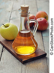 Apple cider vinegar in glass bottle and  fresh apples