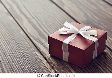 Elegant gift box on a wooden background closeup