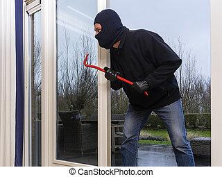Burglar with a crowbar - Mean looking burglar enters a...
