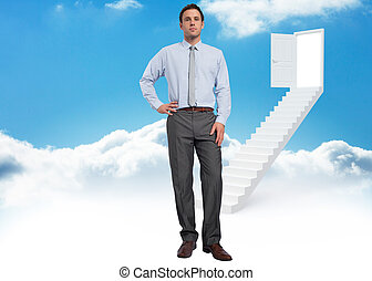 Composite image of serious businessman with hand on hip -...