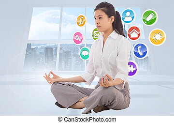 Composite image of businesswoman sitting in lotus pose -...