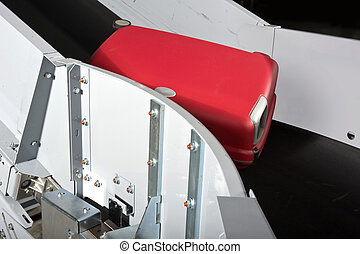 Luggage conveyor belt - A red suitcase on an airport...